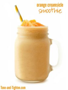 Orange smoothie in a mason jar glass with striped straw isolated on a white background